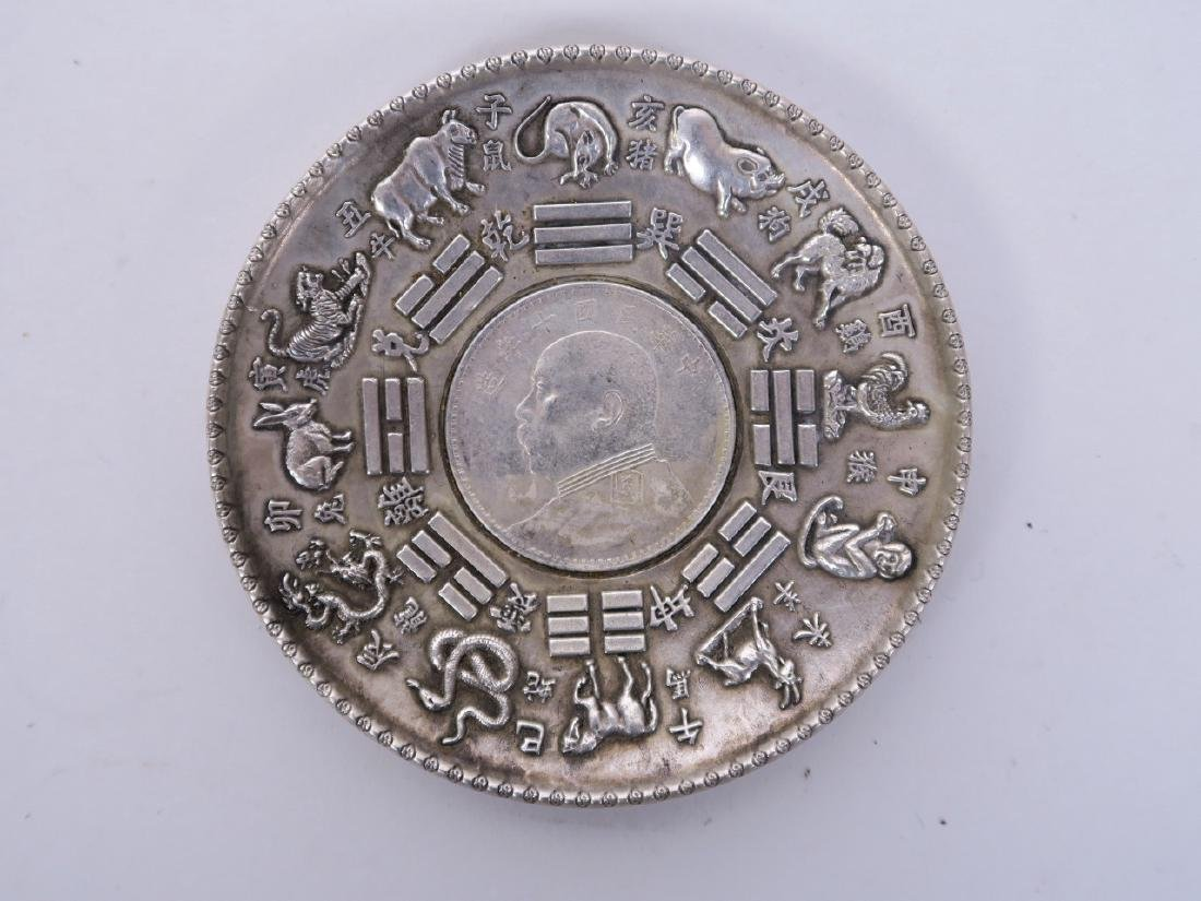 A Chinese white metal coin dish with repoussé zodiac