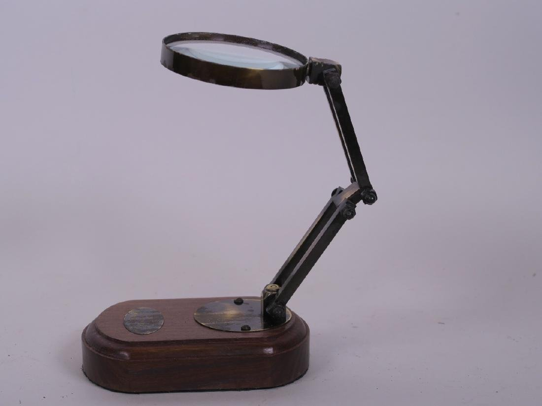 An adjustable brass framed table magnifier on a wooden