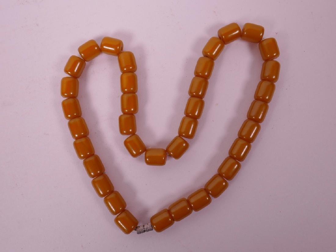 "A butterscotch amber bead necklace, 20"" long"