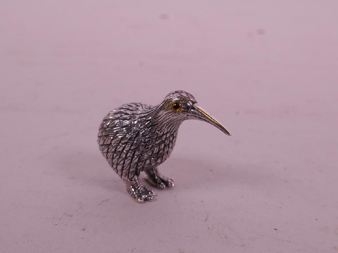 A small silver figure of a kiwi bird with glass eyes,