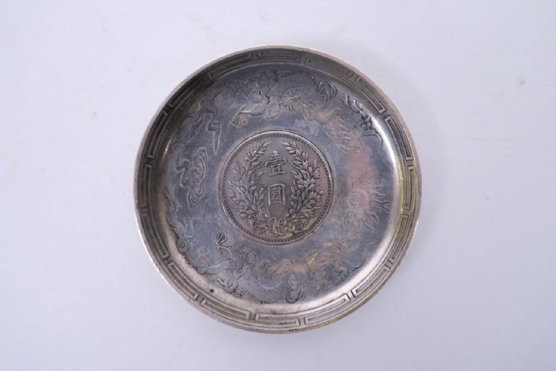 A Chinese white metal coin dish with raised decoration
