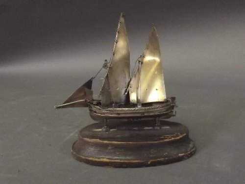 A marked silver sailing boat on wood stand, 5'' high