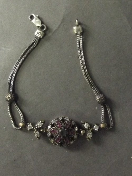 A silver bracelet set with emeralds and ruby flower