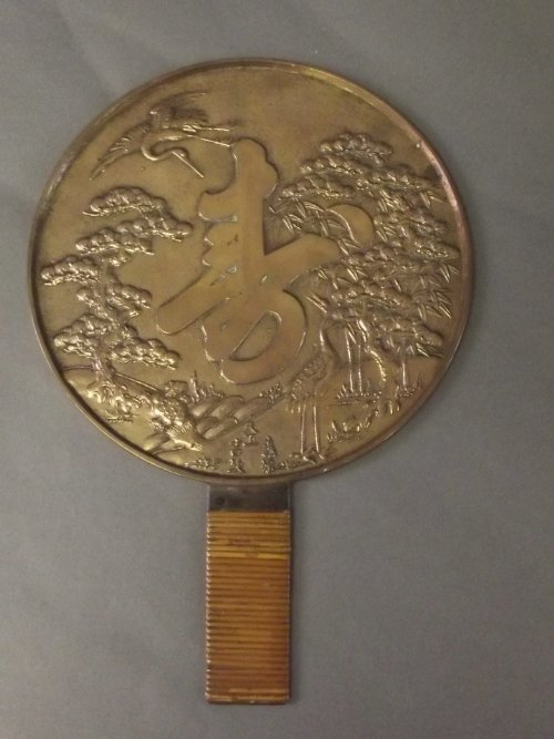 A Chinese metal mirror with reed bound handle, decorate