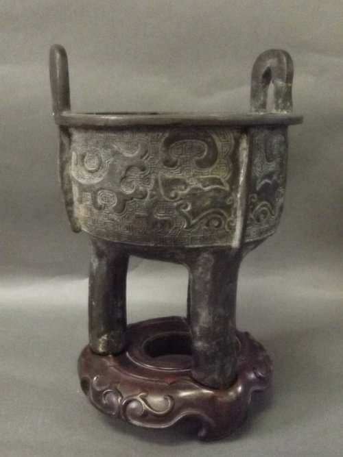 A Chinese bronze tripod legged censer on a carved wood