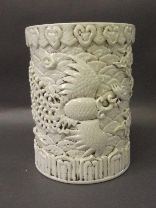 A Chinese cream ground brush pot decorated with raised