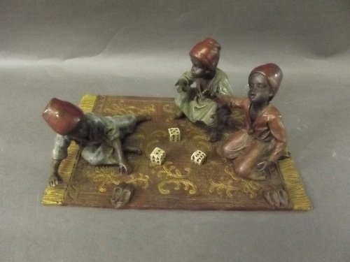 A cold painted bronze figure of three seated boys playi