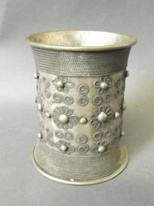 An Indian low grade silver flared sleeve with a floral