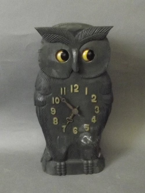 A wooden clock carved in the form of an owl with moving