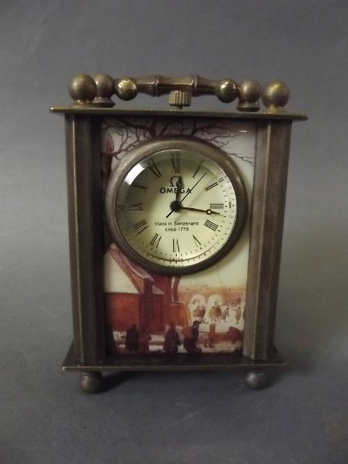 An Omega carriage clock with panels decorated with