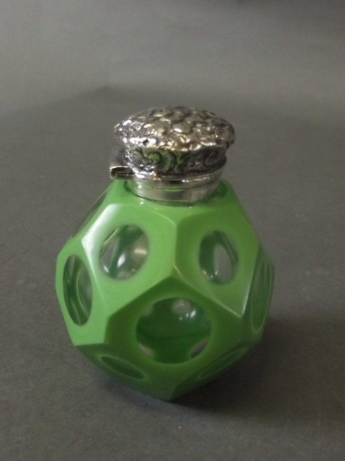 An overlaid faceted glass scent bottle with a silver