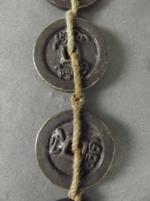 A string of 10 Chinese coins, 17''