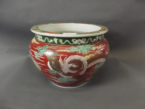 A large C19th Japanese pottery jardinière, red ground