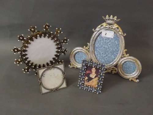 Four small decorative photo frames with ornate enameled