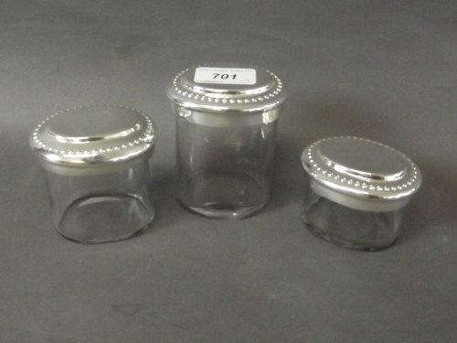A set of 3 glass boxes with silver plated lids, of
