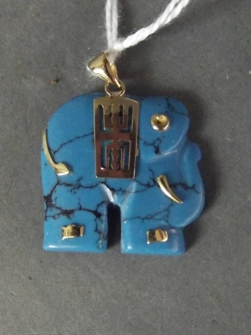 An 18ct gold and turquoise stone pendant carved in the
