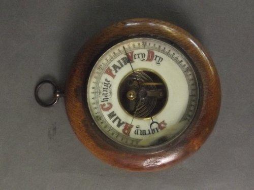 A circular barometer in an oak surround, 5½'' diameter