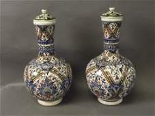 A pair of Turkish pottery vases and covers with hand