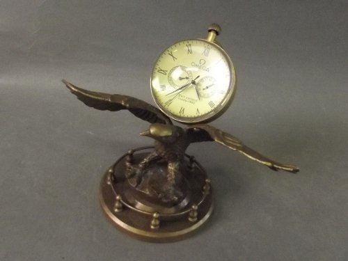 An Omega glass orb clock mounted on the back of a brass