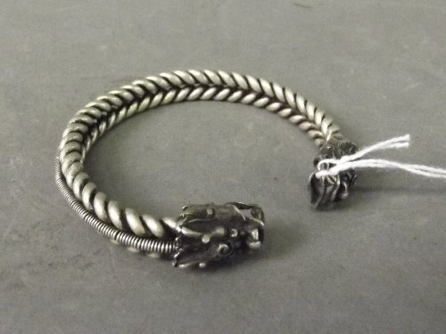 A Chinese white metal half bangle in the form of a rope