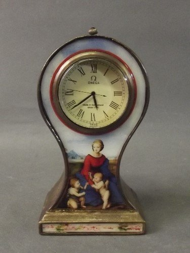 A brass Omega desk clock decorated with an enamel panel