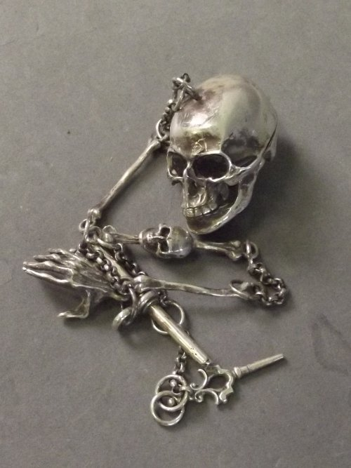 A silver watch chain in the form of a skull with garnet