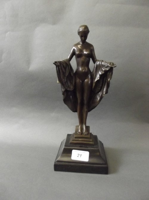 A bronze figure of a nude woman in a draped robe,
