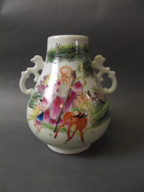 A Chinese twin handled vase decorated with a sage and 2
