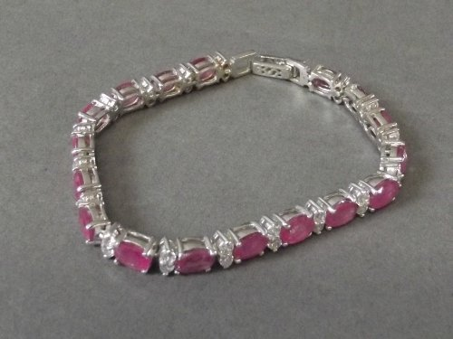 A silver and real ruby line set bracelet, 7'' long