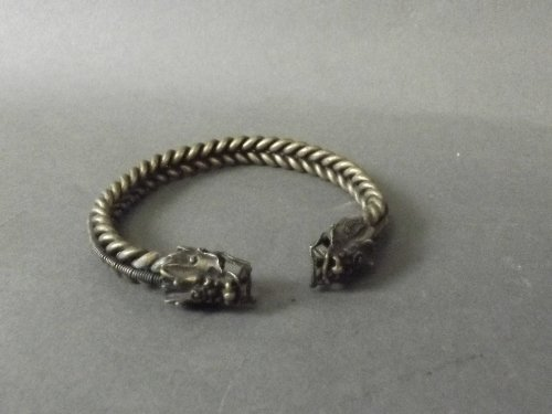 A Chinese white metal rope bangle with dragon head
