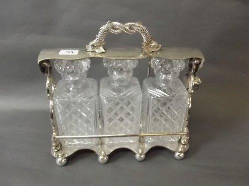 A good silver plated tantalus enclosing 3 cut glass