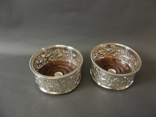 A pair of ornate silver plated wine coasters, 5½''