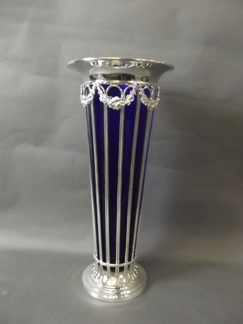 A large silver plated pierced vase with a blue glass