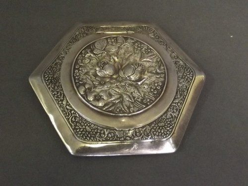 A Chinese white metal compact with floral decoration to