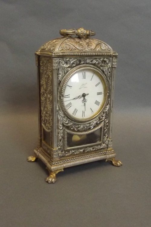 An ornate gilt metal mantle clock on pawed feet support