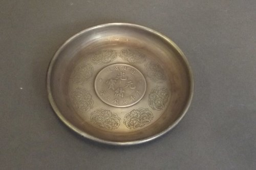 A Chinese silvered metal dish with a Chinese coin set t