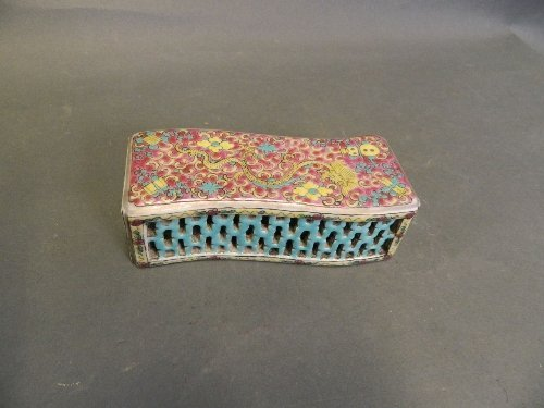 A Chinese famille rose pierced wrist rest with a