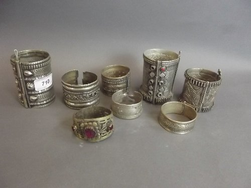 Eight Eastern white metal amulets and bangles with