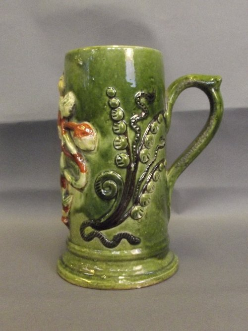 An English pottery tankard with raised decoration of a