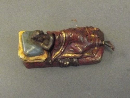 A cold painted bronze figure of a naked sleeping girl