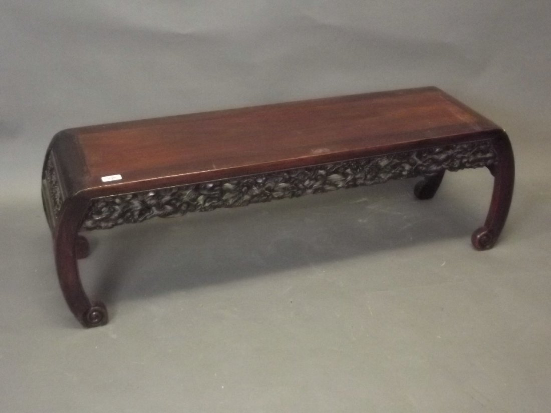 A Chinese hardwood low occasional table with carved and