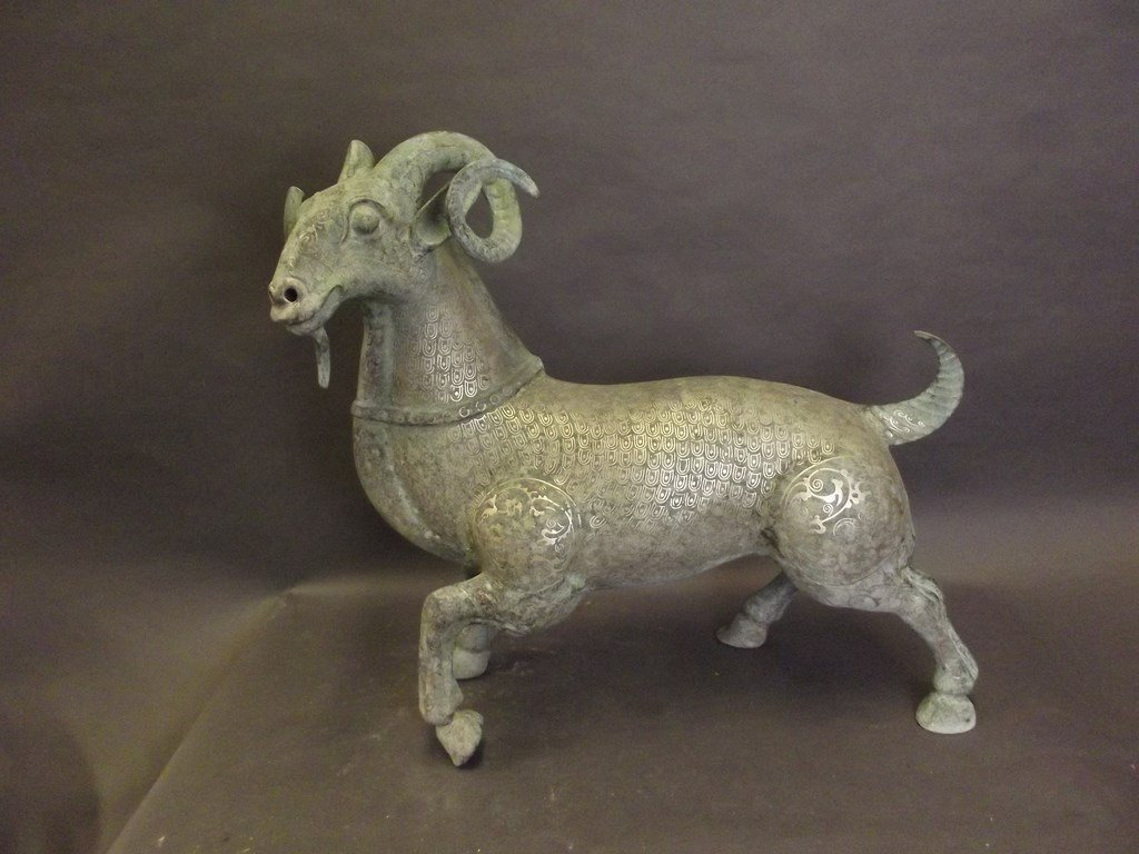 A Middle Eastern metal figure of a ram with intricate