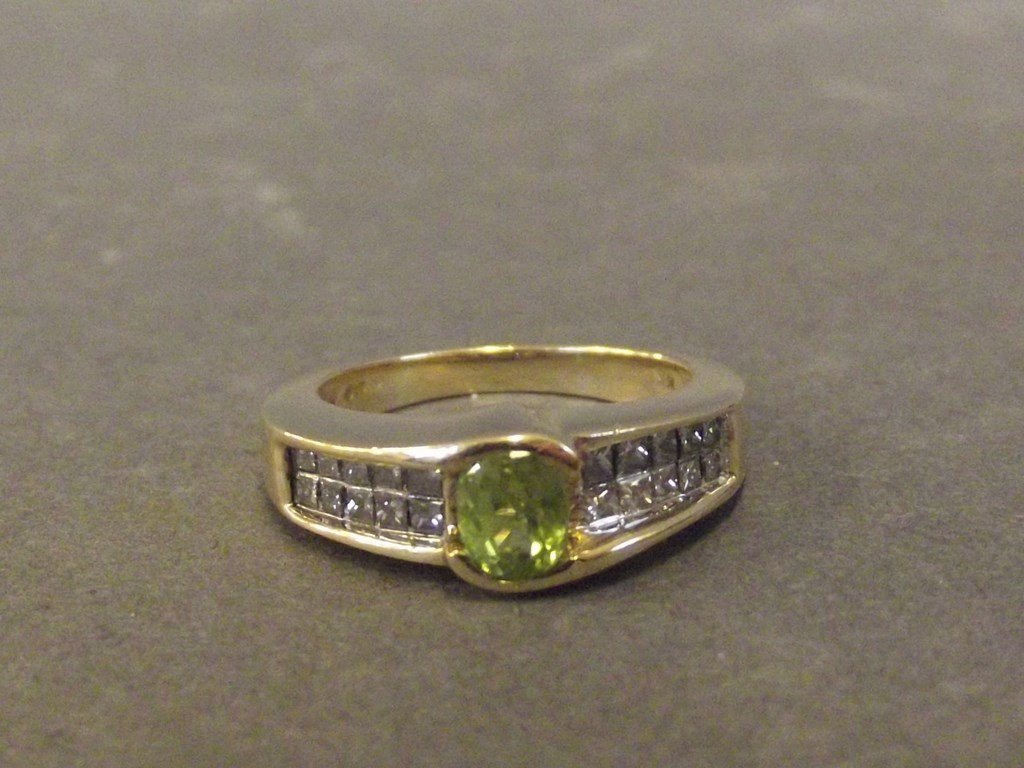 A 14ct gold peridot diamond ring with Chanel set