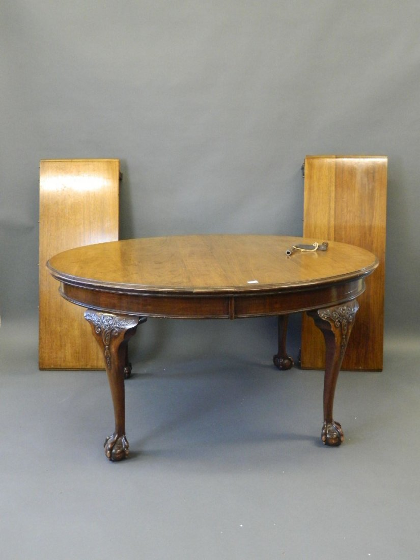 A Victorian oval walnut wind out dining table with two
