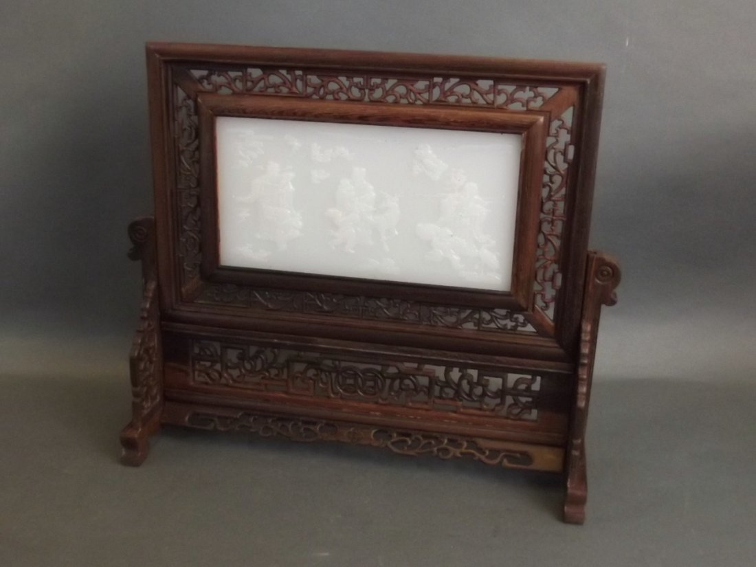 A Chinese carved and pierced hardwood and white jade