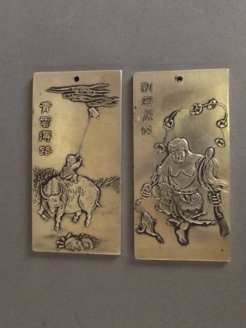 A pair of Chinese silver metal scroll weights with