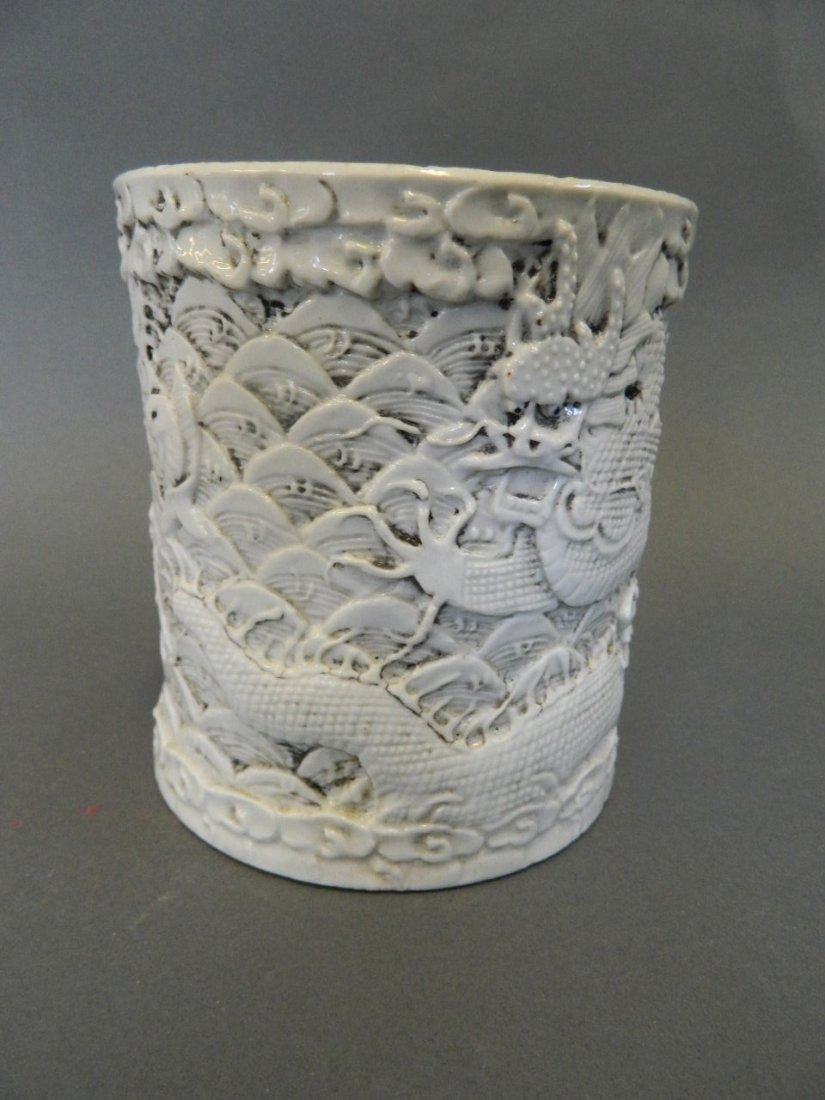 A Chinese white glazed porcelain brush pot with carved