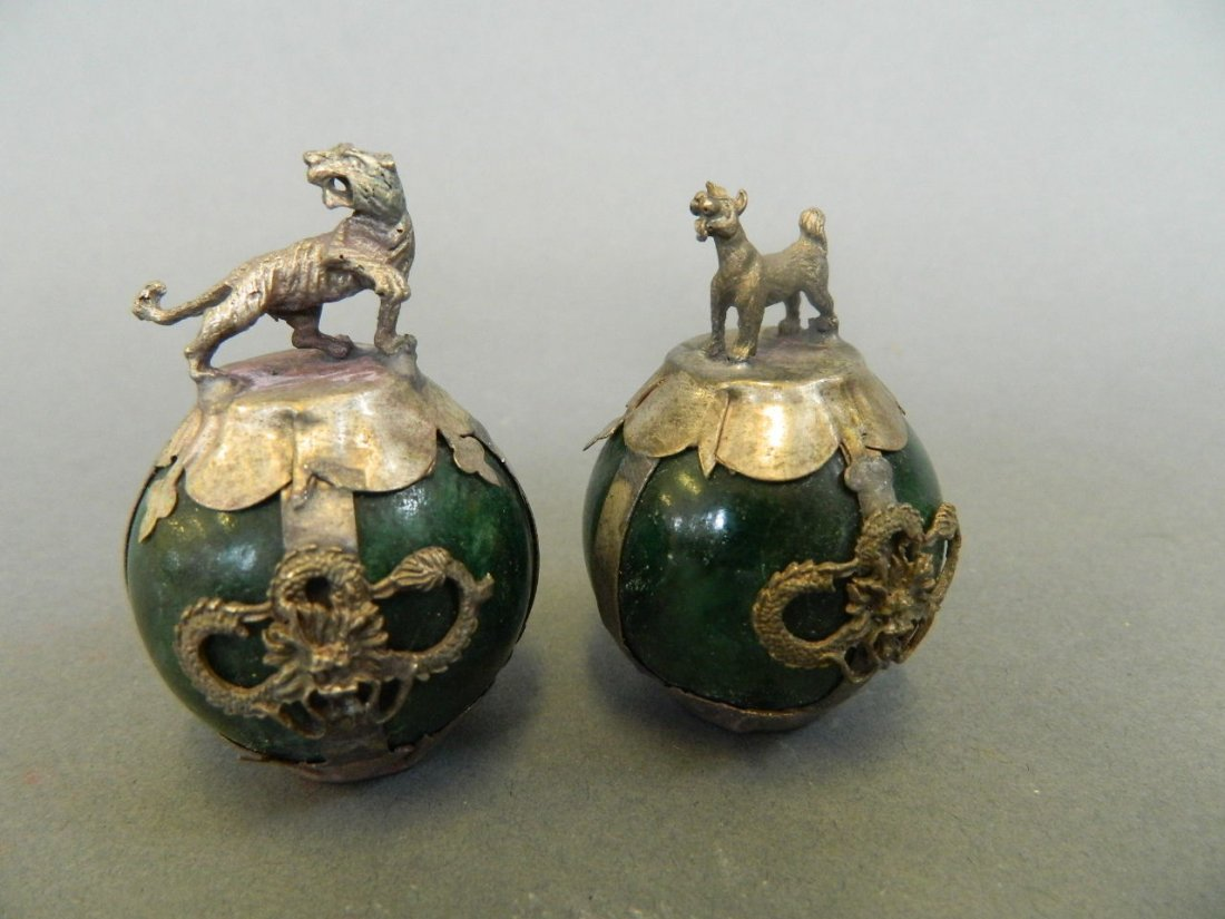A pair of Chinese jade ball paperweights encased in
