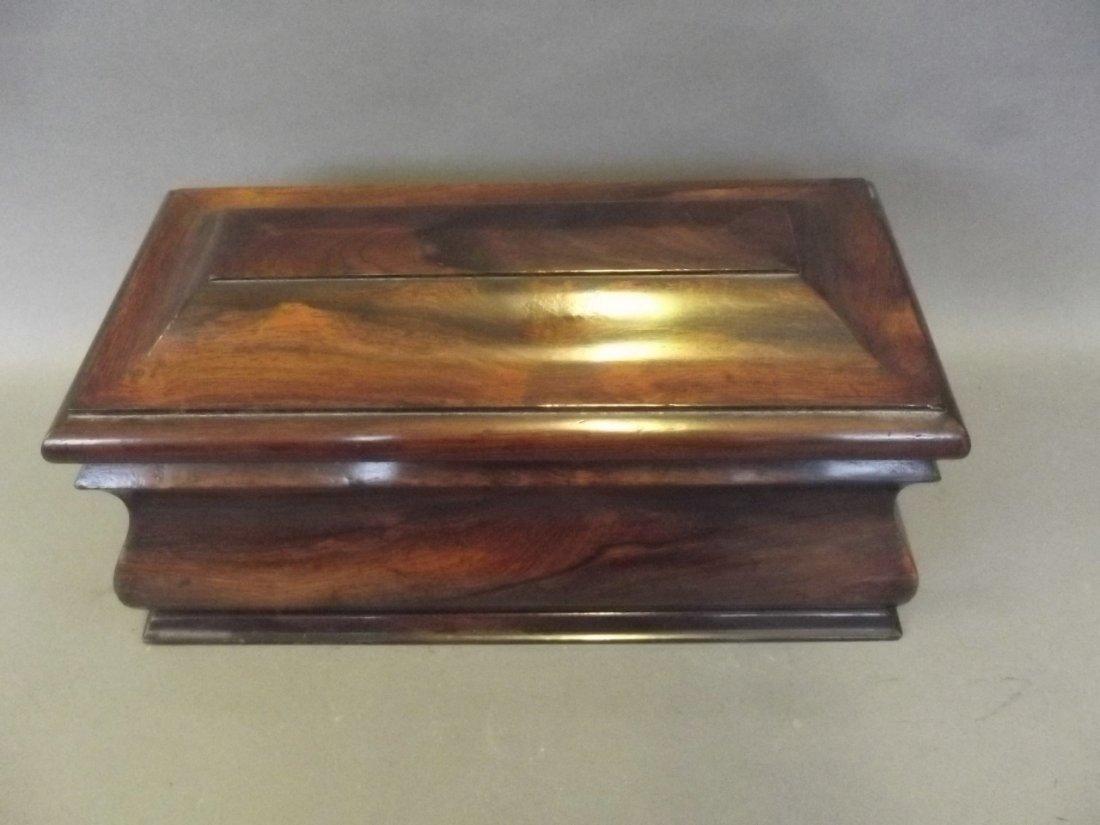 A Regency bombé shaped rosewood twin compartment tea