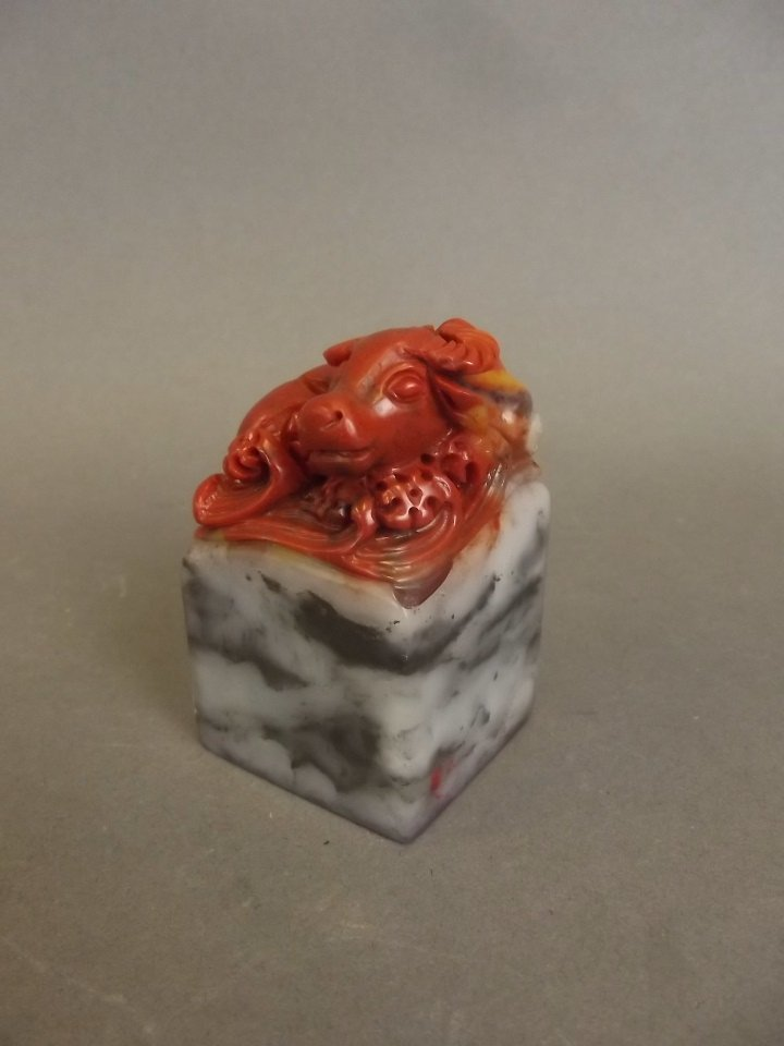 A Chinese chicken blood soapstone seal with carved